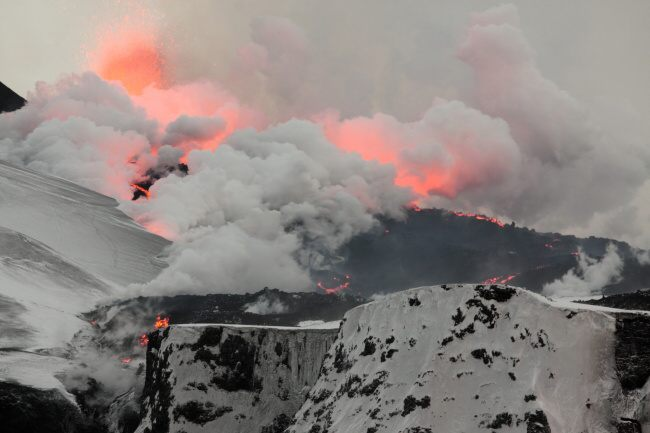 Erupce sopky Eyjafjallajökull, duben 2010, pohled jak láva teče po ledovci k severu a mění sníh na páru.